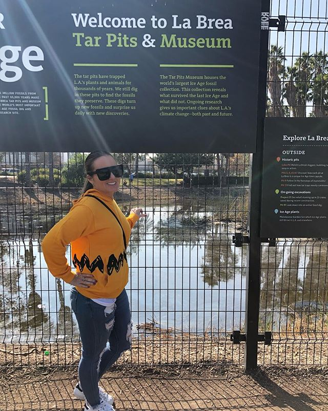 Woman posing with the welcome sign for La Brea Tar Pits and Museum in LA in California. | 1 Week in Los Angeles, California