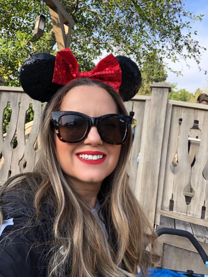 Woman with Minnie Mouse ears on taking a selfie.| What to Wear to Disneyland