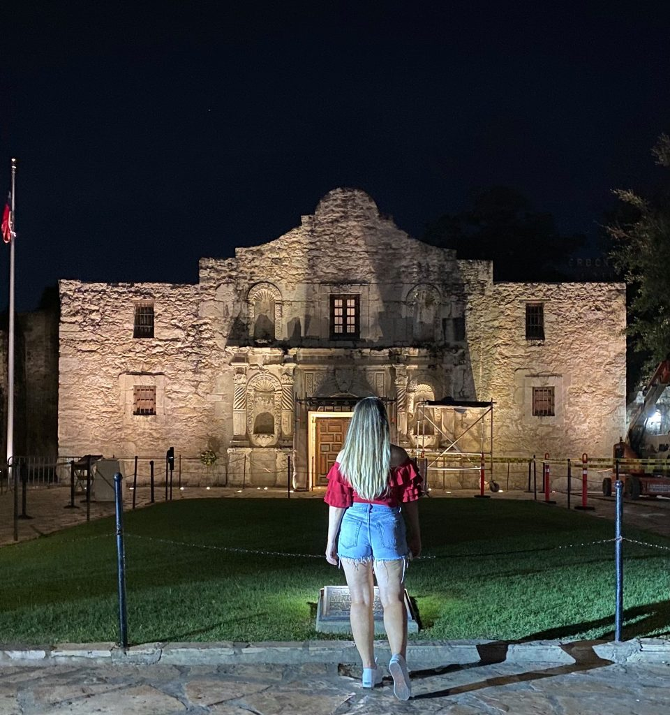 Woman standing with her back to the camera looking at an old building at night. Hotel Valencia Riverwalk: My Trip to San Antonio