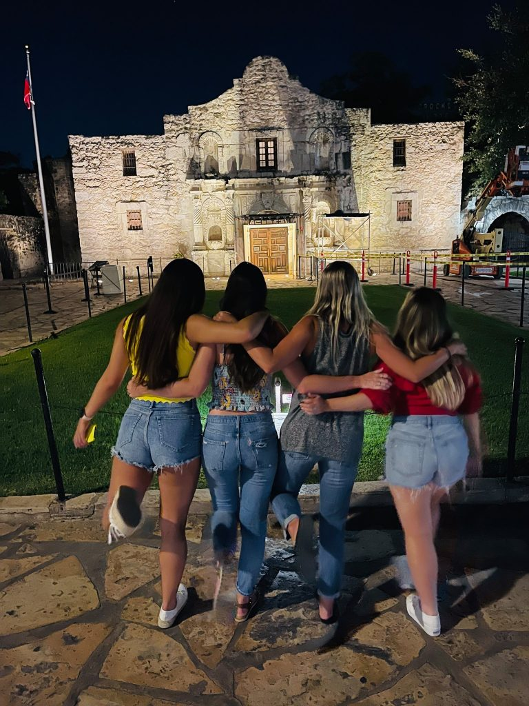 Four women facing away from the camera facing the old building. Hotel Valencia Riverwalk: My Trip to San Antonio