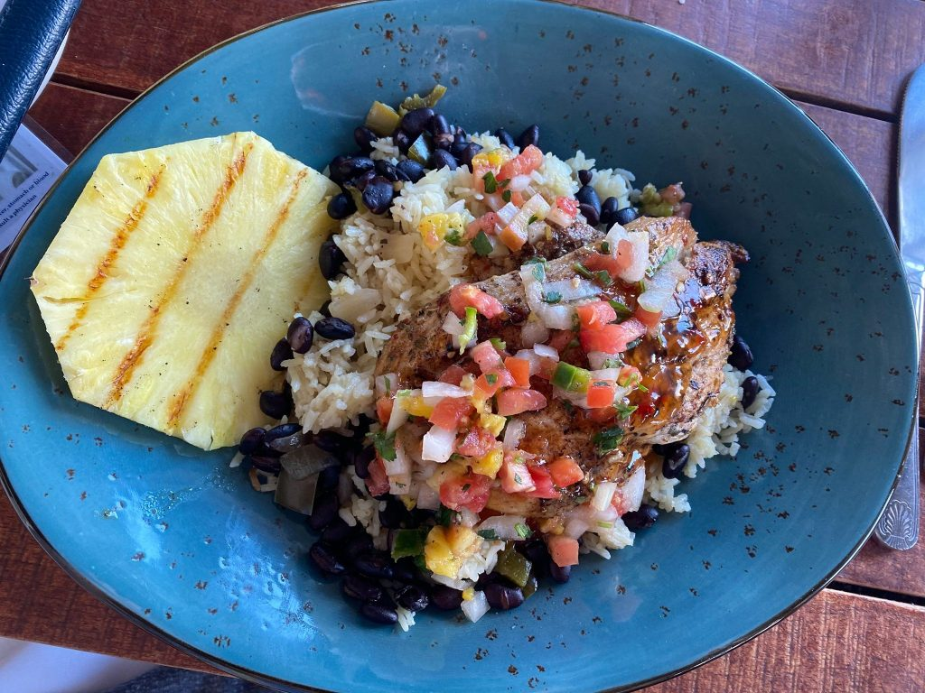 Plate of fish, rice and salsa with a side of pineapple.   Where to Eat in Key West