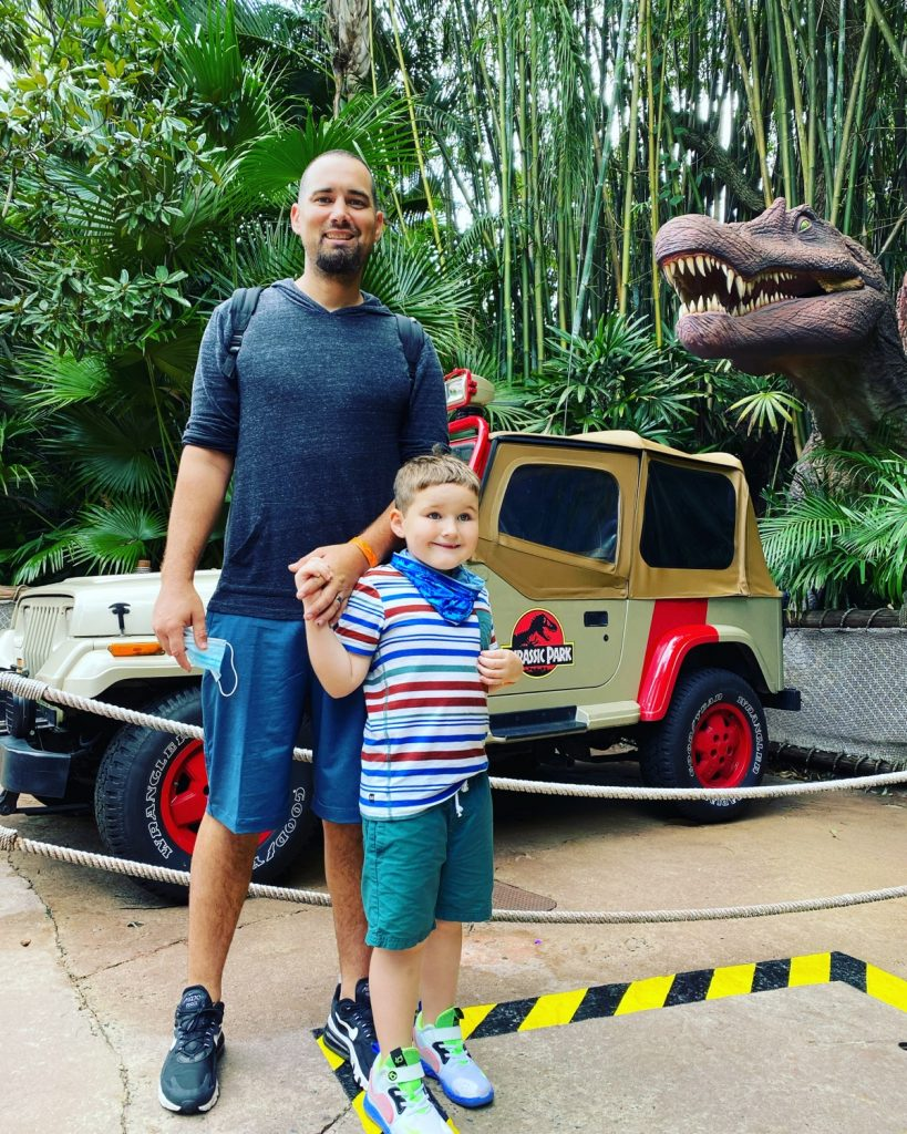 Dad with his son in front of the Jurassic Park Jeep and Dinosaur.  Universal's Islands of Adventure with Kids