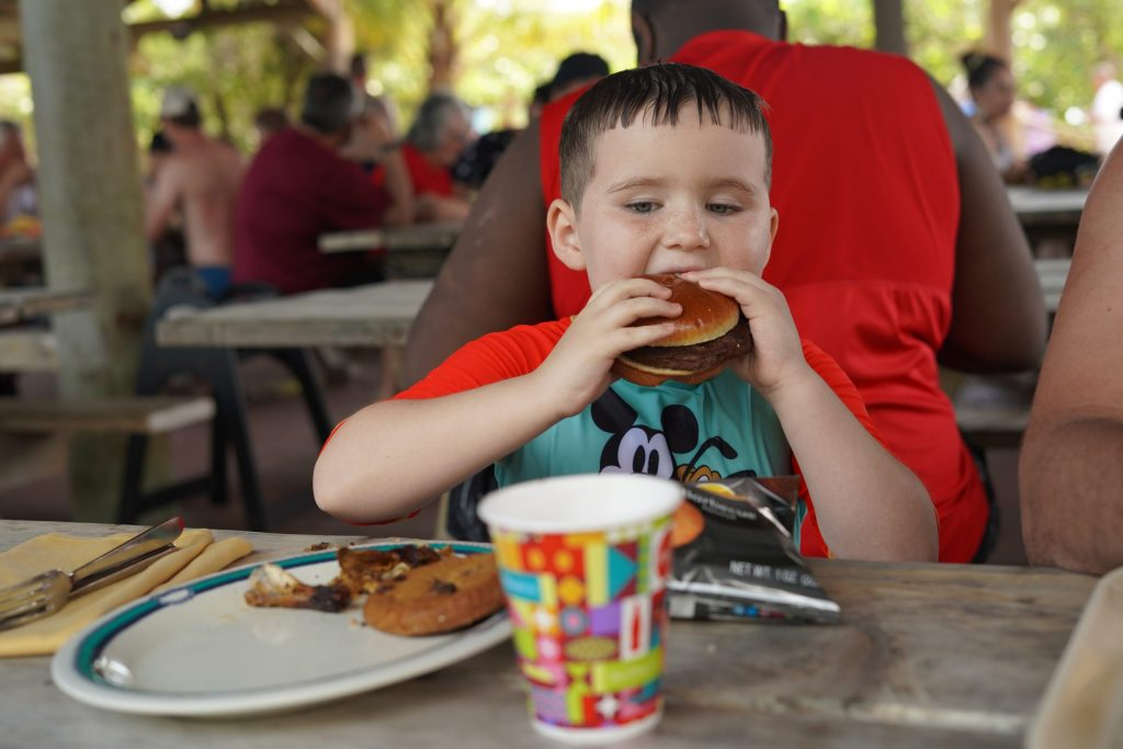 Little boy eating a hamburger on the island. | Castaway Cay- Everything you need to know