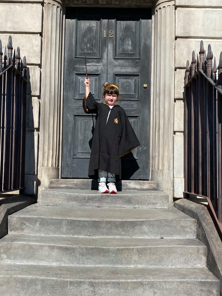 Little girl dressed like Harry Potter with a wand in front of large door in Universal Studios.   A Guide to Universal Studios Orlando with Kids