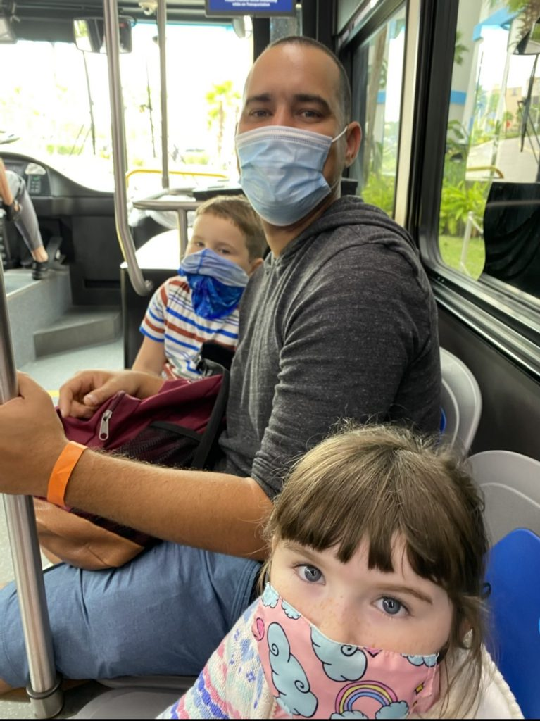 Dad with two kids riding the bus with masks on.   Universal's Islands of Adventure with Kids