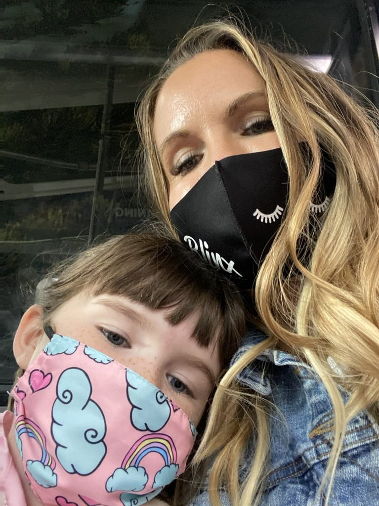 Mom with her daughter riding the bus with masks on.   Universal's Islands of Adventure with Kids