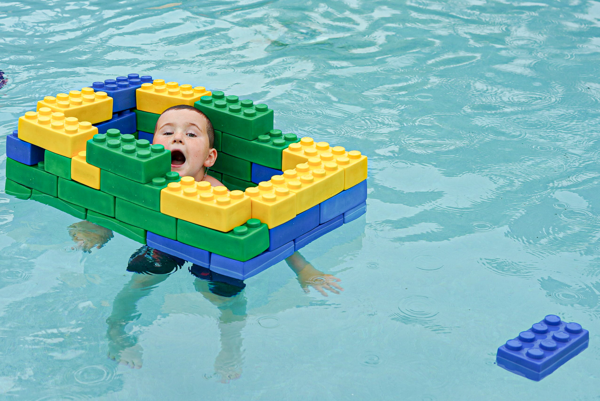 Little boy floating with a lego float in the pool.   A Guide to LEGOLAND Hotels in Florida