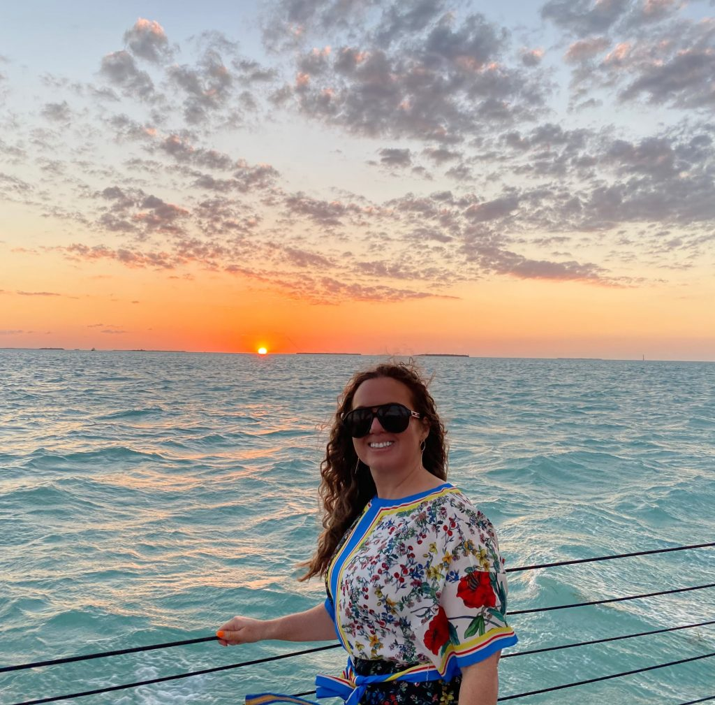 Woman posing on a boat with the sunset behind her.   What to expect on a Key West Sunset Cruise, on a Schooner America Sailboat