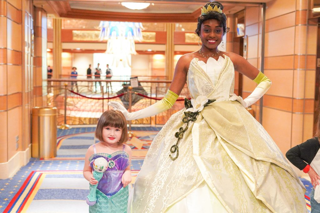 Little girl posing with Tiana character on the cruise ship. | Disney Dream Cruise