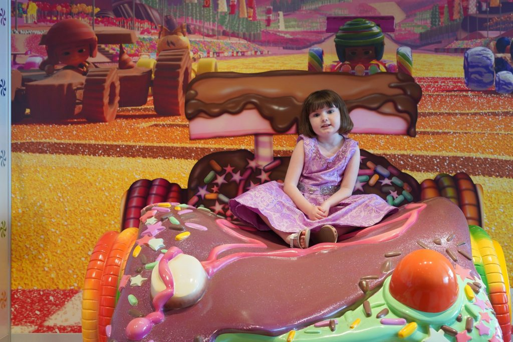 Little girl sitting on candy bed on the Disney cruise. | Disney Dream Cruise
