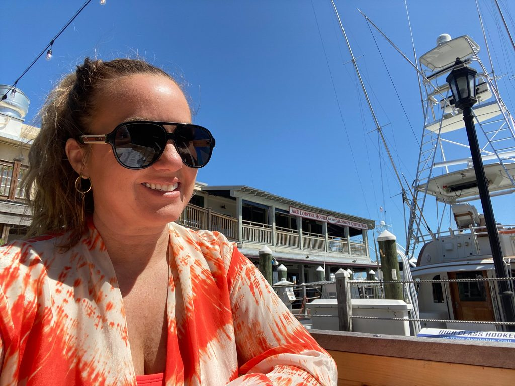 Woman smiling outside with a boat behind her.   Where to Eat in Key West