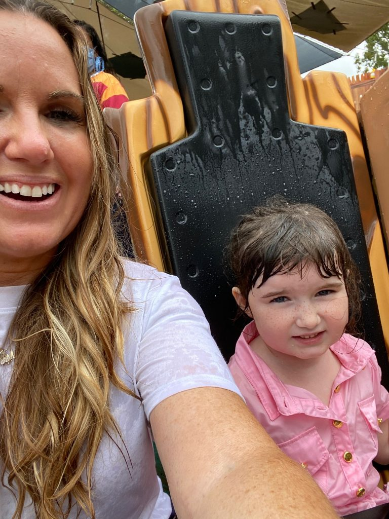 Woman with a little girl on a water ride soaking wet after the ride, taking a selfie together.   Universal's Islands of Adventure with Kids
