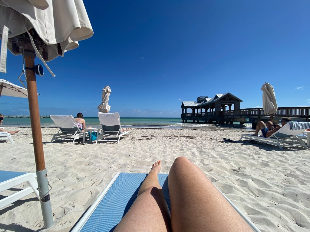 Woman laying on the beach with lounge chairs with ocean view, in Key West. | What you to need to know about Key West