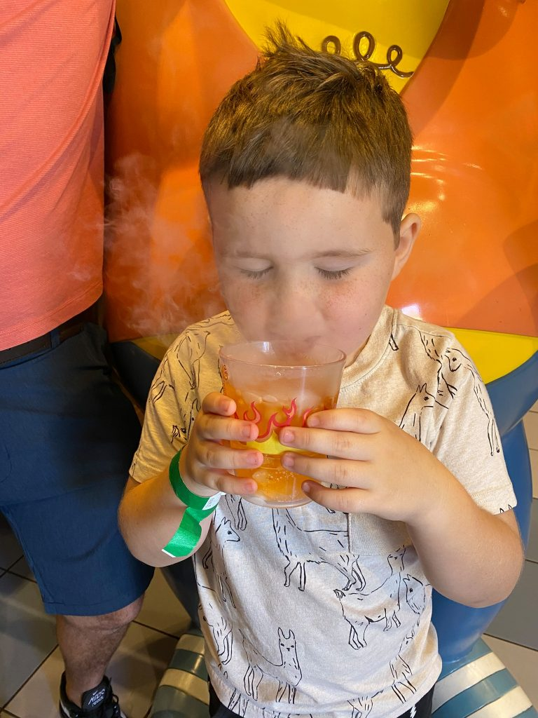 Little boy drinking a drink with dry ice in Moe's Tavern in Universal Studios.   A Guide to Universal Studios Orlando with Kids