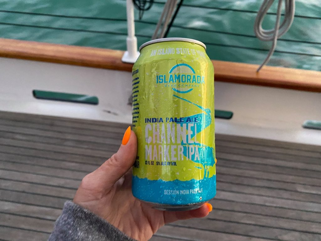 Woman holding can of India Pale Ale Channel Marker PA   What to expect on a Key West Sunset Cruise, on a Schooner America Sailboat
