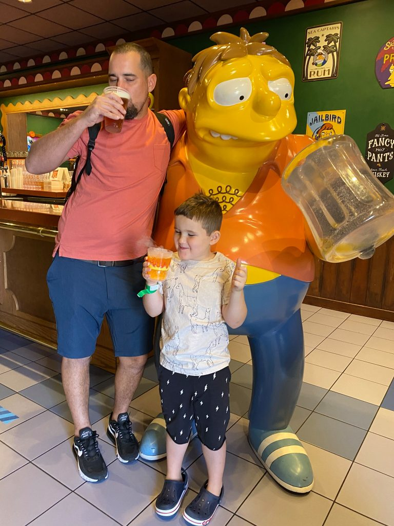 Dad drinking a beer with son drinking a drink with a character from the Simpsons in Moe's Tavern in Universal Studios.   A Guide to Universal Studios Orlando with Kids