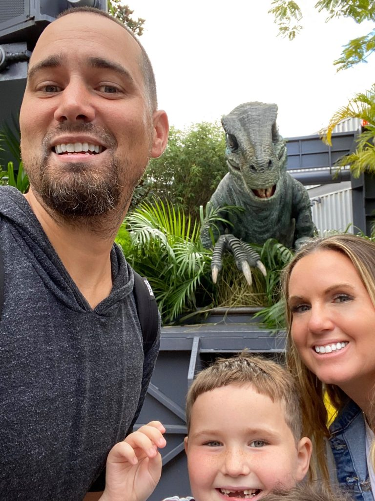 Man, woman and little boy taking a selfie in front of a dinosaur statue.   Universal's Islands of Adventure with Kids