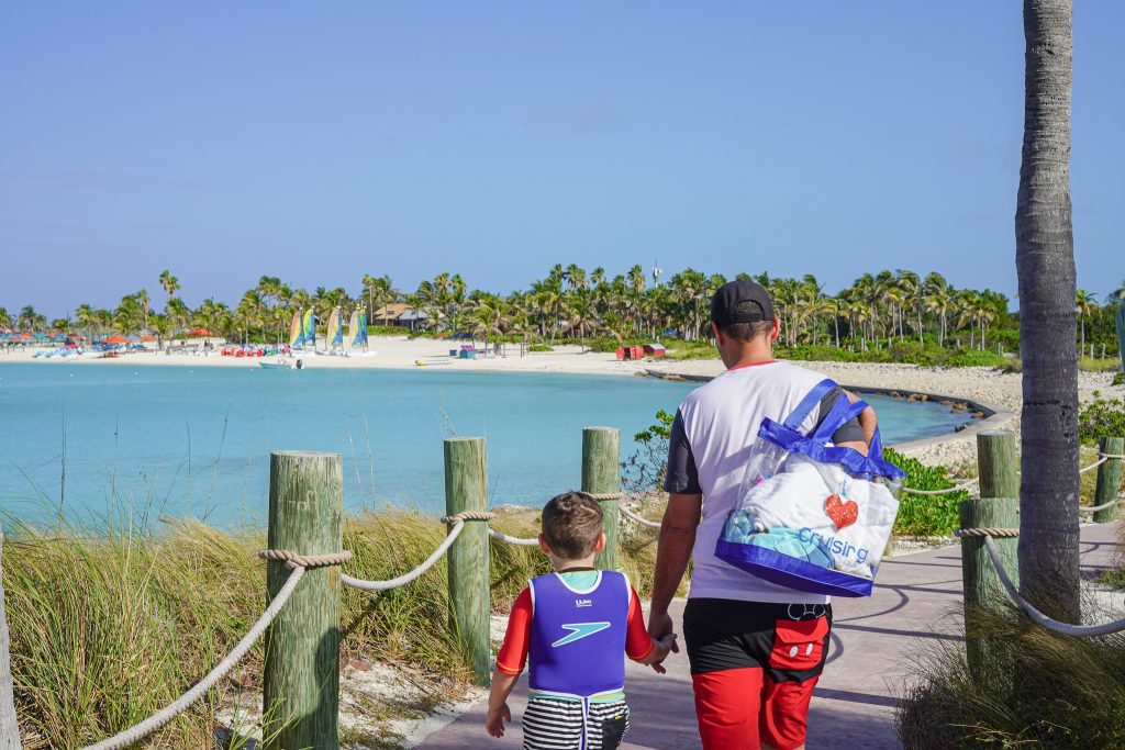 Man with son walking on the boardwalk near the beach. | Castaway Cay- Everything you need to know