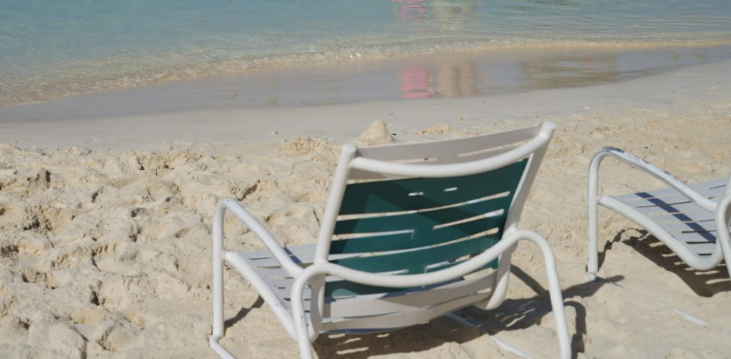 Beach chairs in the sand by the water. | Castaway Cay- Everything you need to know