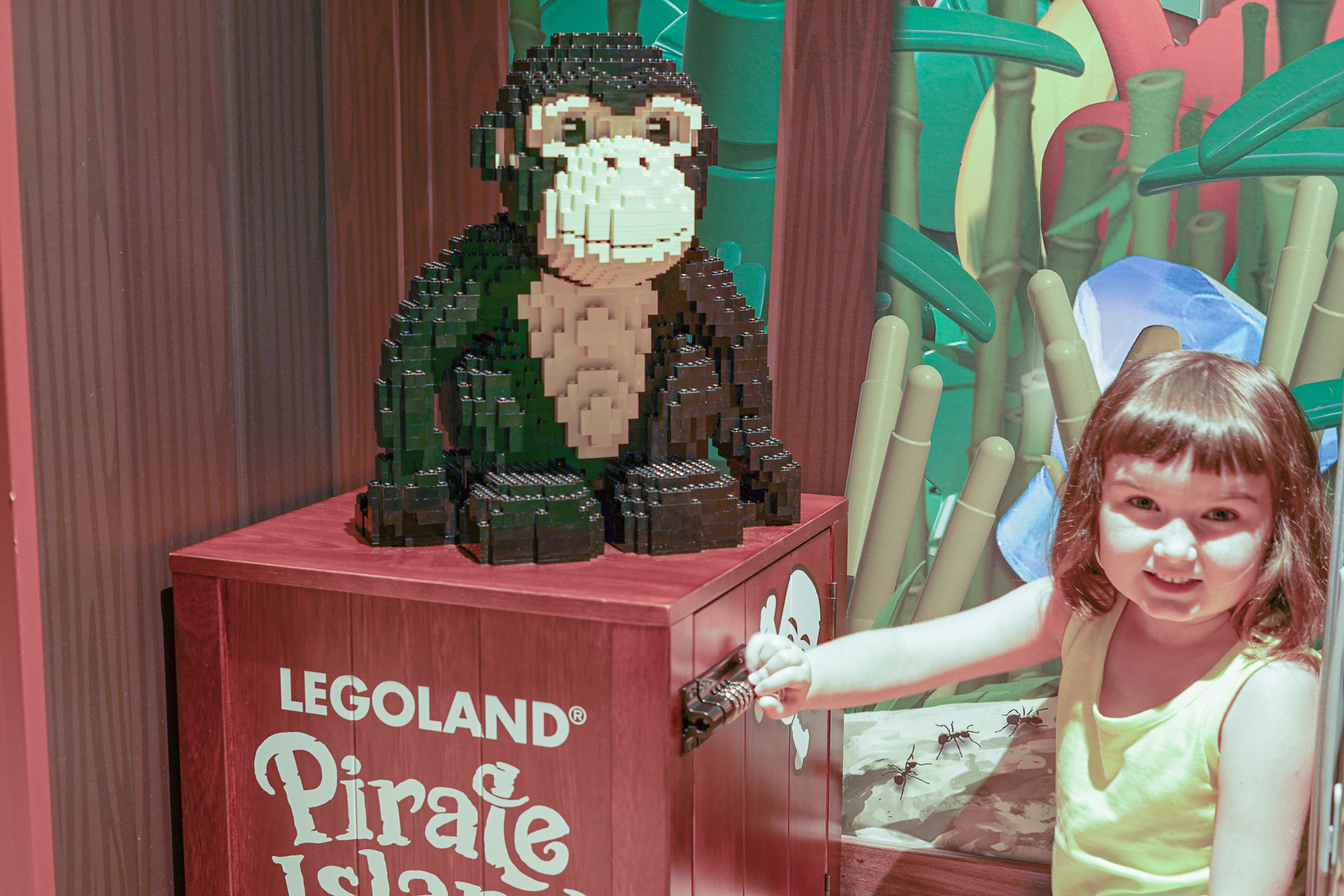 Little girl with a lego monkey at Pirate Island Hotel.   A Guide to LEGOLAND Hotels in Florida