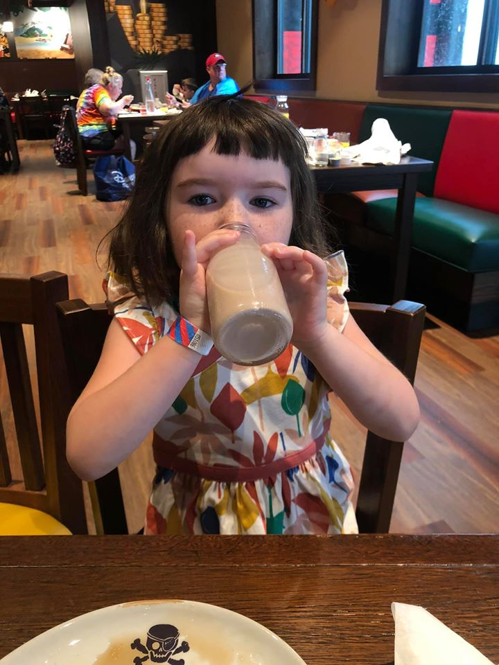 Little girl drinking chocolate milk at Shipwreck restaurant at Pirate Island Hotel.   A Guide to LEGOLAND Hotels in Florida