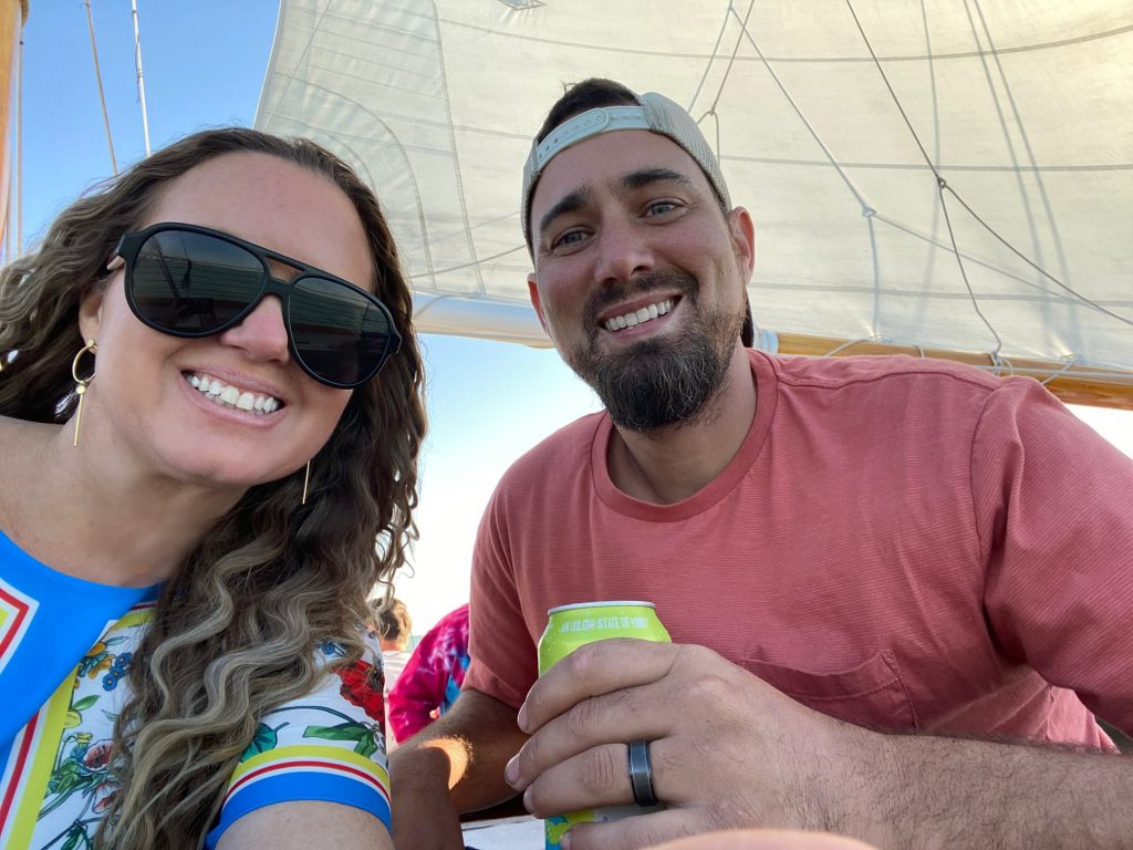 Couple smiling at the camera on a boat in Key West.   What to expect on a Key West Sunset Cruise, on a Schooner America Sailboat