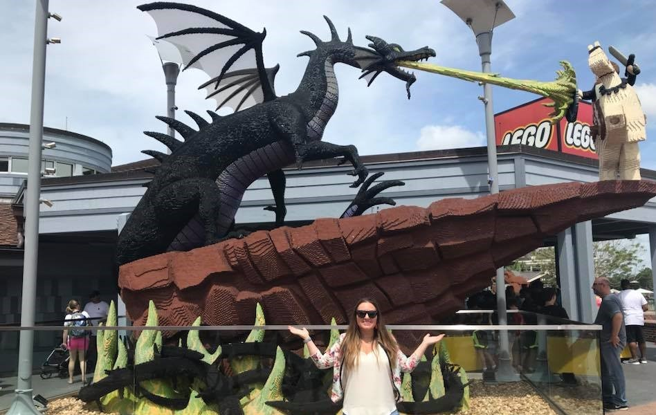 Woman posing in front of Lego dragon character at Disney Springs at Disney World.   Disney World- What you need to know.