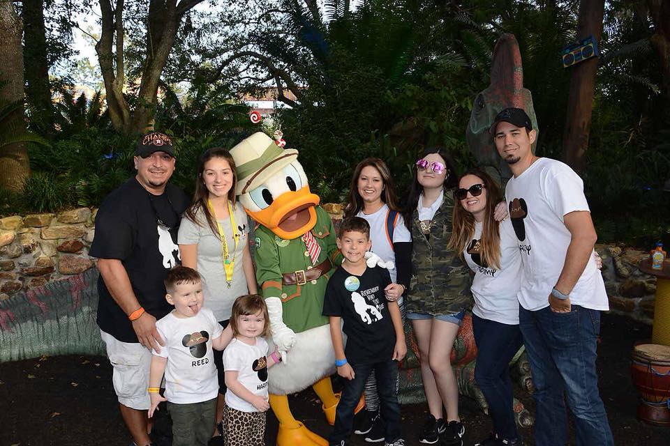 Family and friends posing with Donald Duck character outside at Disney World.   Disney World- What you need to know.