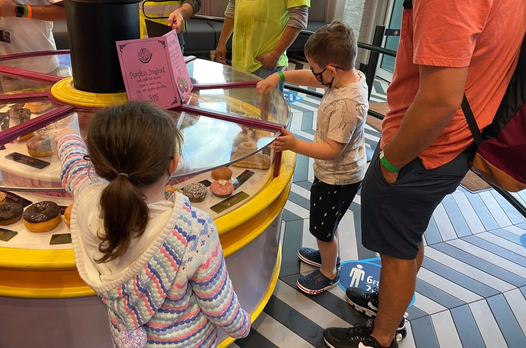 Two little kids looking at the different flavors of donuts in the Voodoo donutshop. | What to eat at Universal's Citywalk in Orlando