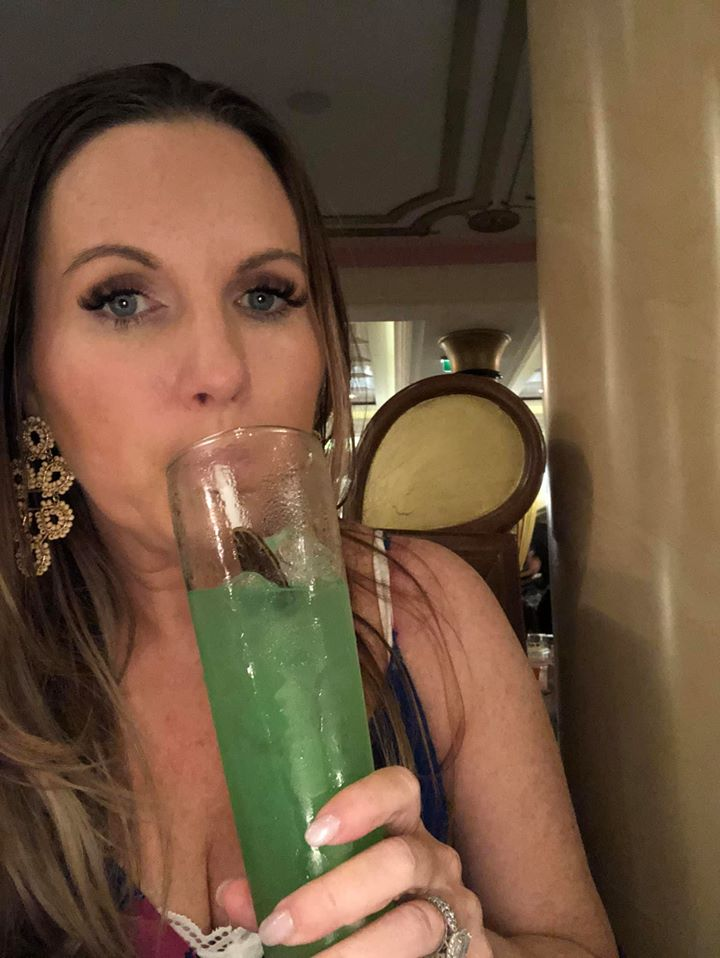 Woman drinking a cocktail on the Disney cruise. | Disney Dream Cruise