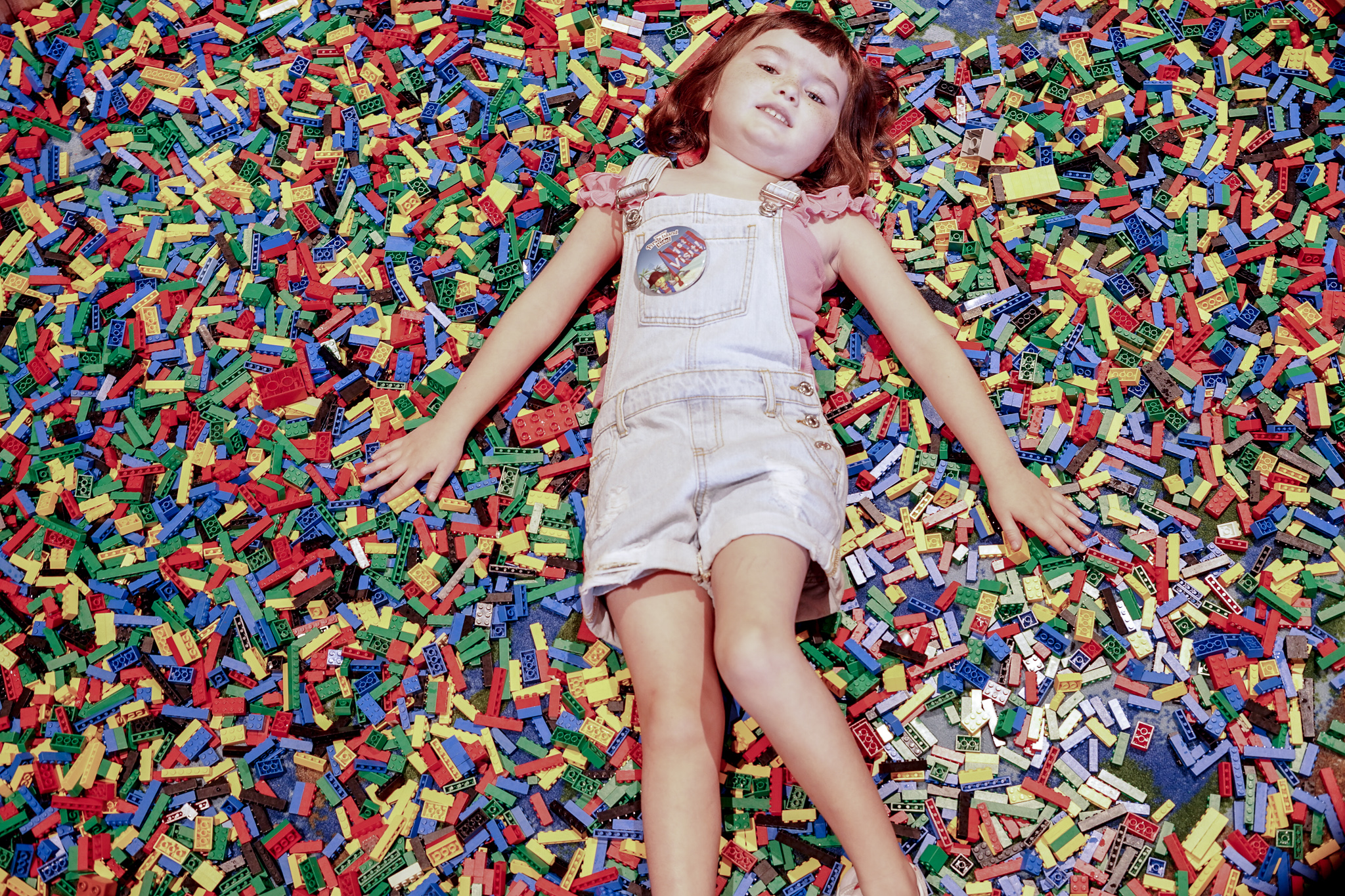 Little girl laying in a huge pile of legos.  | Guide to LEGOLAND Florida