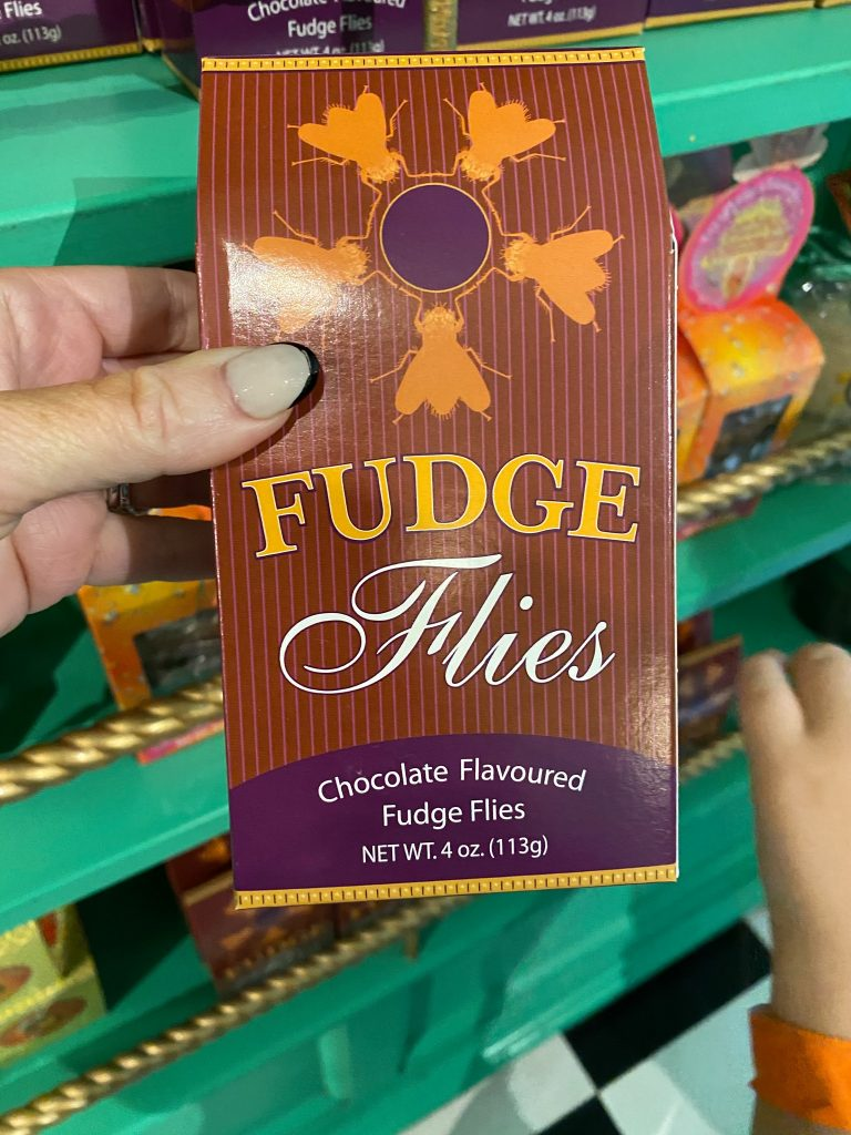 Woman holding a box of fudge flies in a store at The World of Harry Potter.   Universal's Islands of Adventure with Kids
