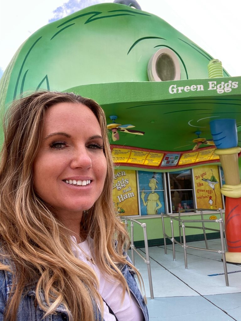 Woman posing in front of Green Eggs and Ham restaurant at Dr. Seuss.   Universal's Islands of Adventure with Kids