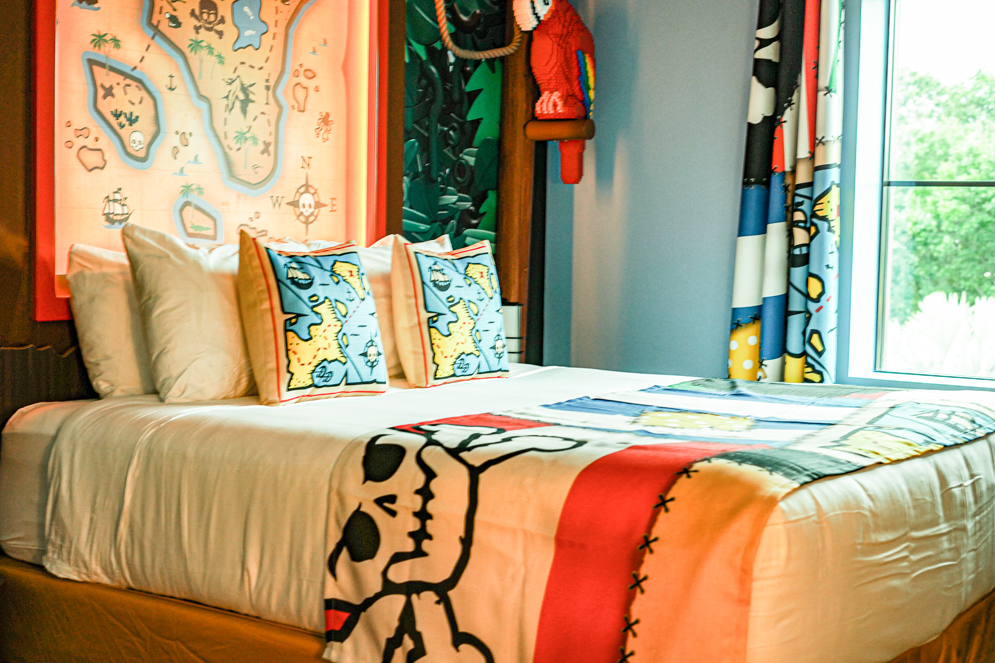 Hotel bed with lego themed bedding and decor.   A Guide to LEGOLAND Hotels in Florida