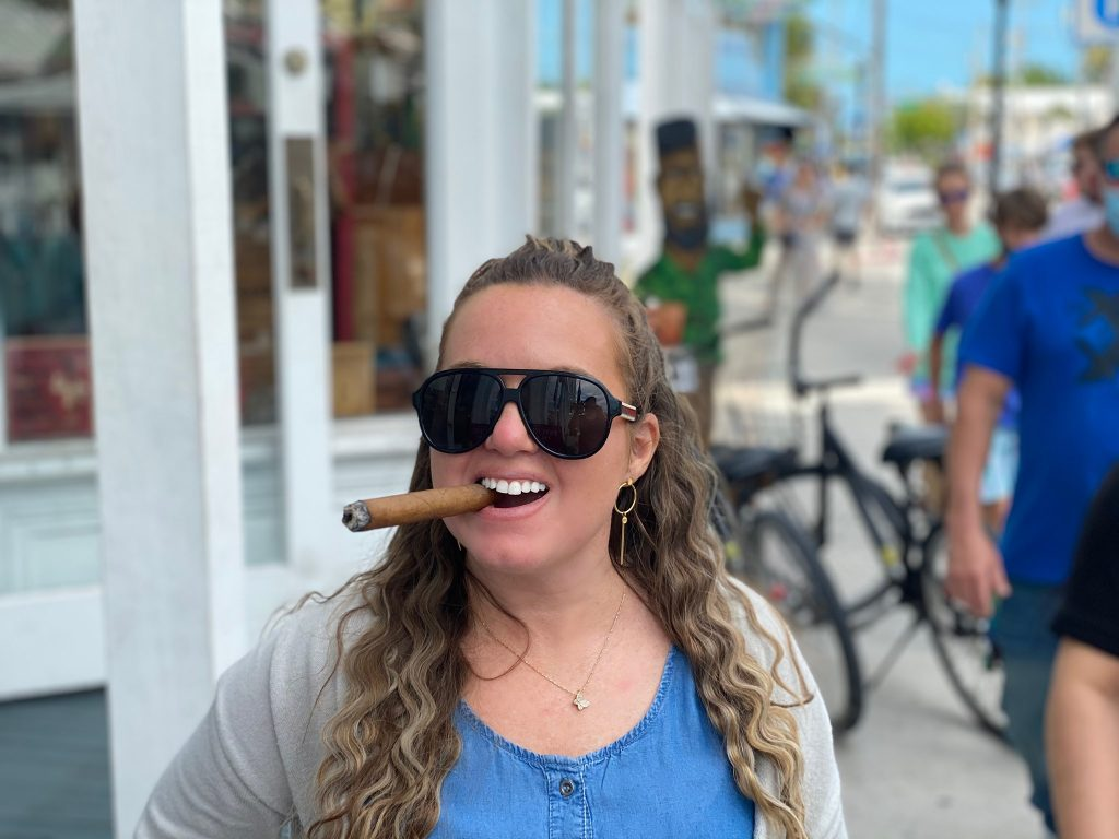 Woman in Key West smoking cigar on street.| What you to need to know about Key West