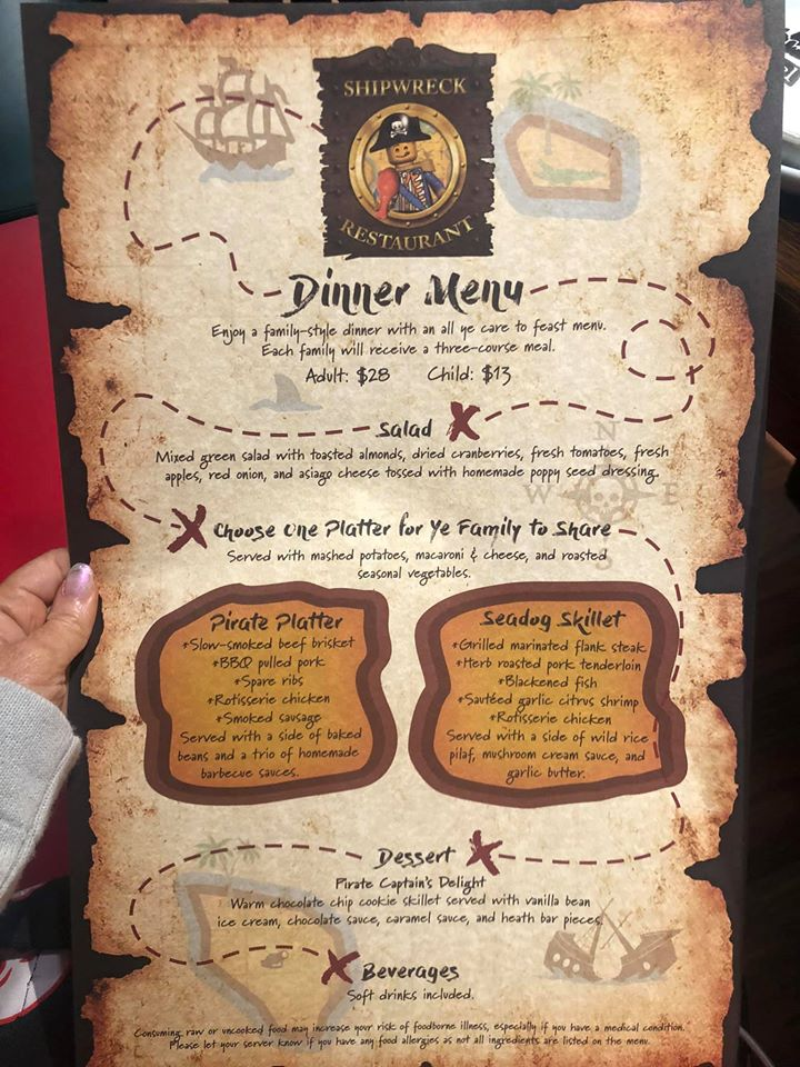 Woman holding the dinner menu at Shipwreck restaurant at Pirate Island Hotel.   A Guide to LEGOLAND Hotels in Florida