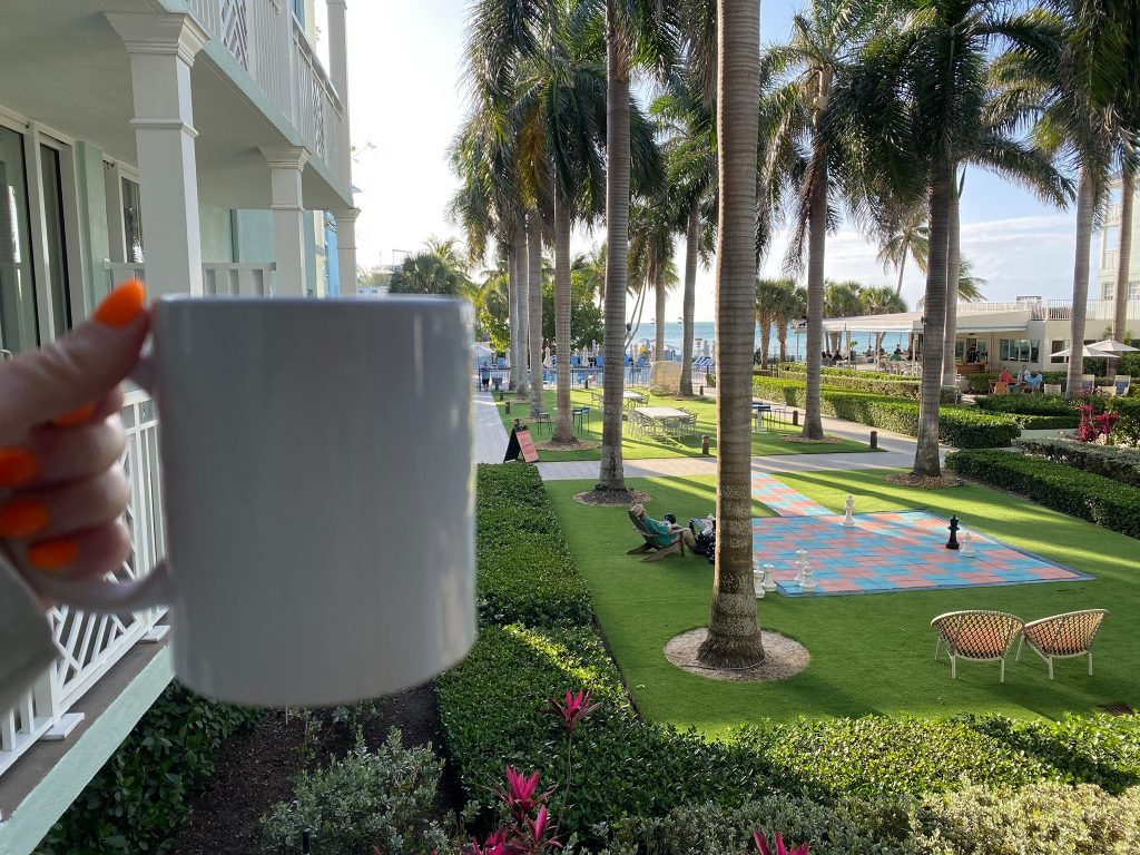 Woman holding coffee mug with hotel lawn view in Key West. | What you to need to know about Key West
