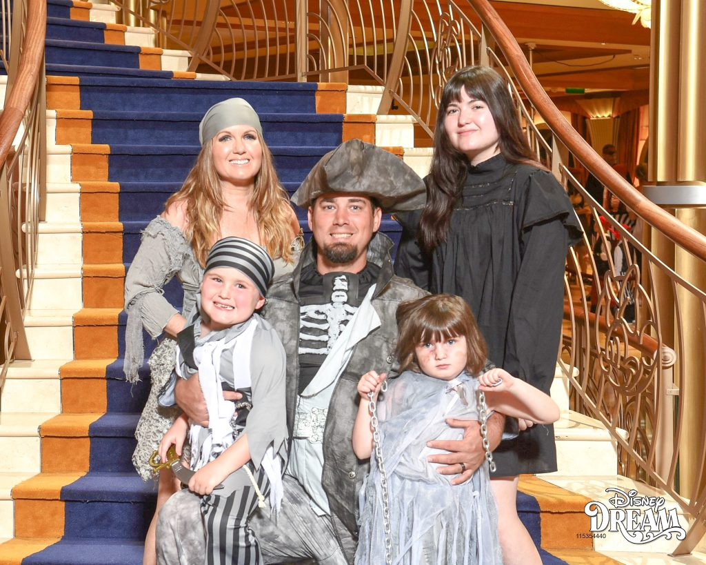 Family posing on the stairs for the pirate themed night on the cruise ship. | Disney Dream Cruise