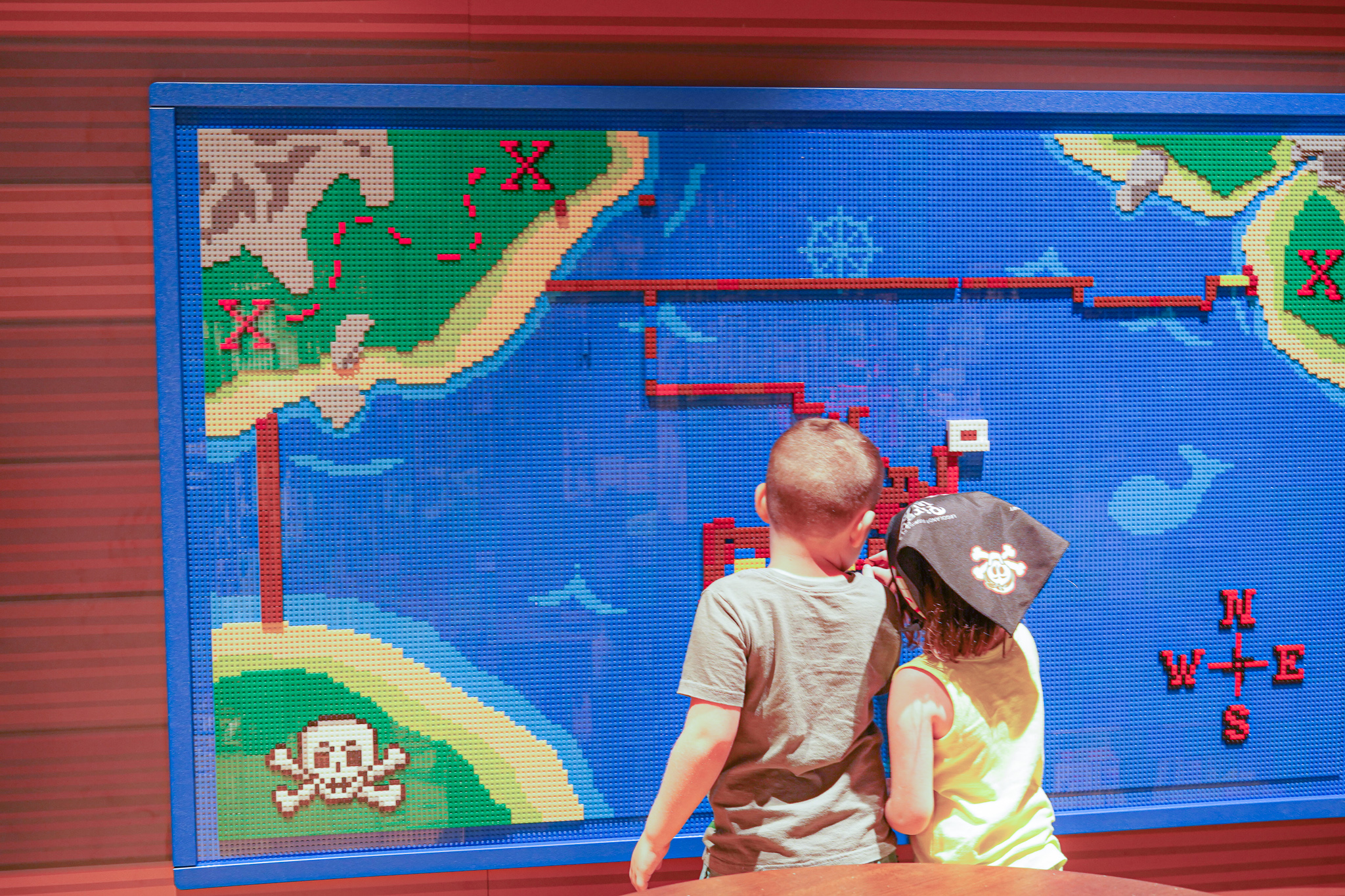 Two kids playing games at Pirate Island Hotel.   A Guide to LEGOLAND Hotels in Florida