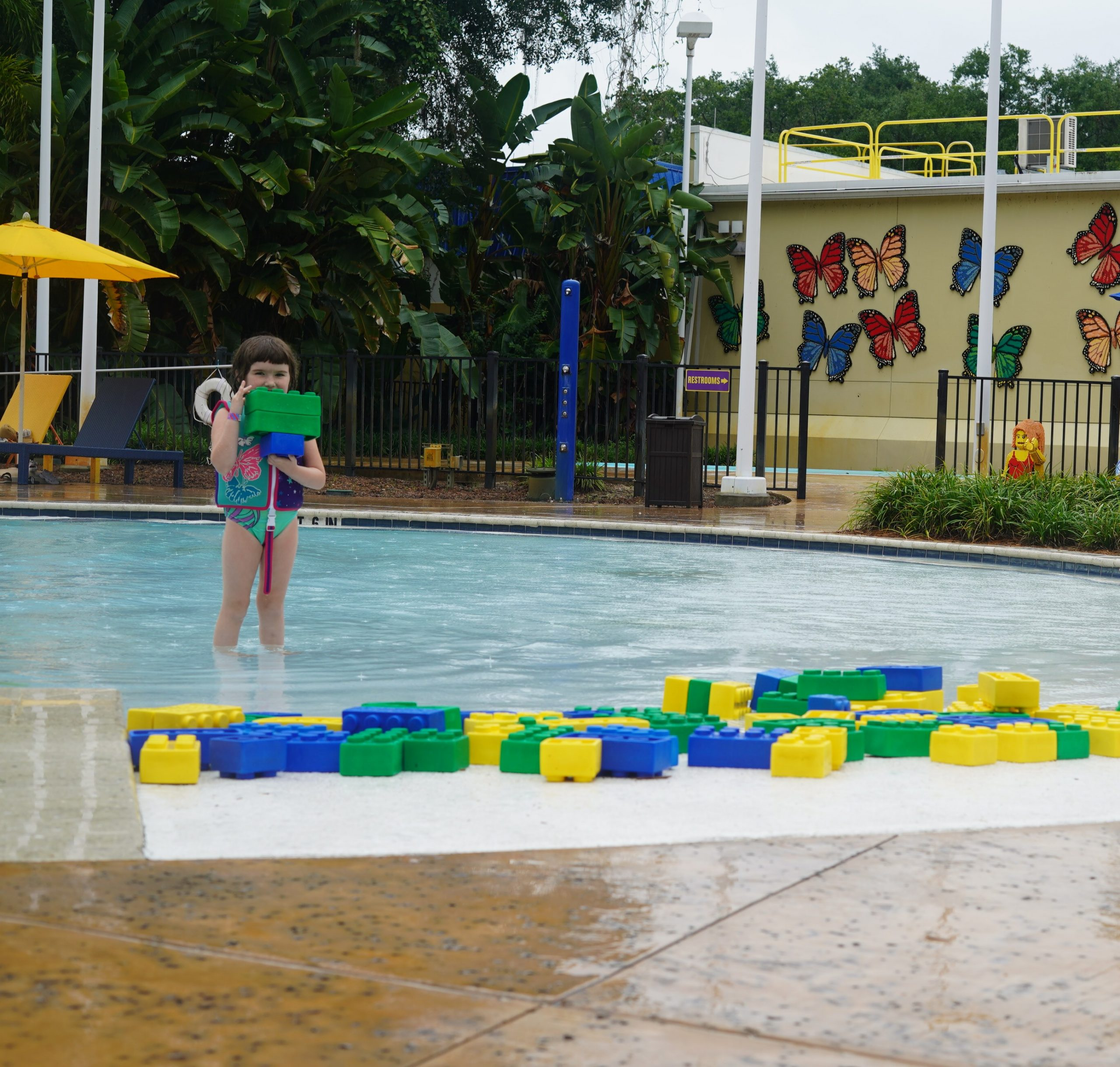 Little girl playing with lego floats at the pool at Pirate Island Hotel.   A Guide to LEGOLAND Hotels in Florida