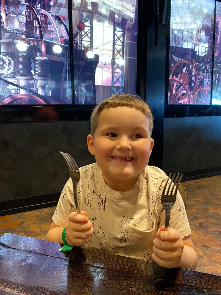 Little boy smiling and excited food holding two forks in his hands at the Toothsome Chocolate Factory restaurant. | What to eat at Universal's Citywalk in Orlando