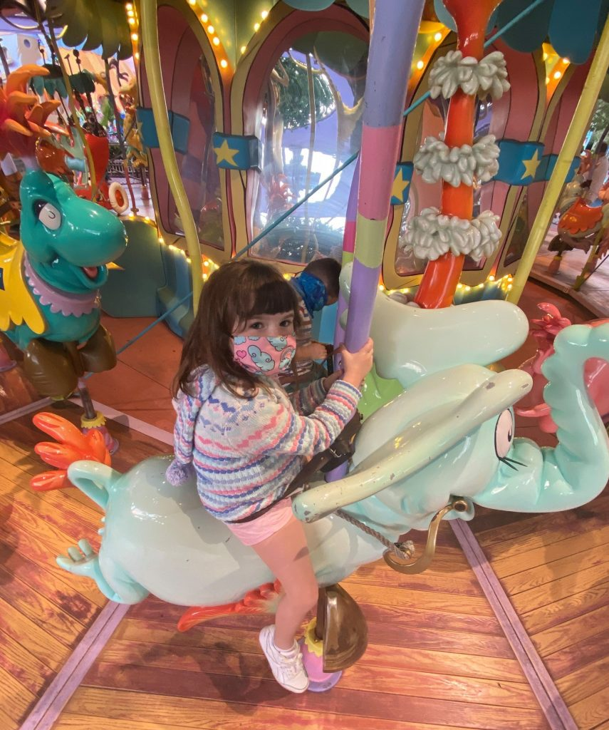 Little girl riding an elephant on a merry-go-round at Dr. Seuss.   Universal's Islands of Adventure with Kids
