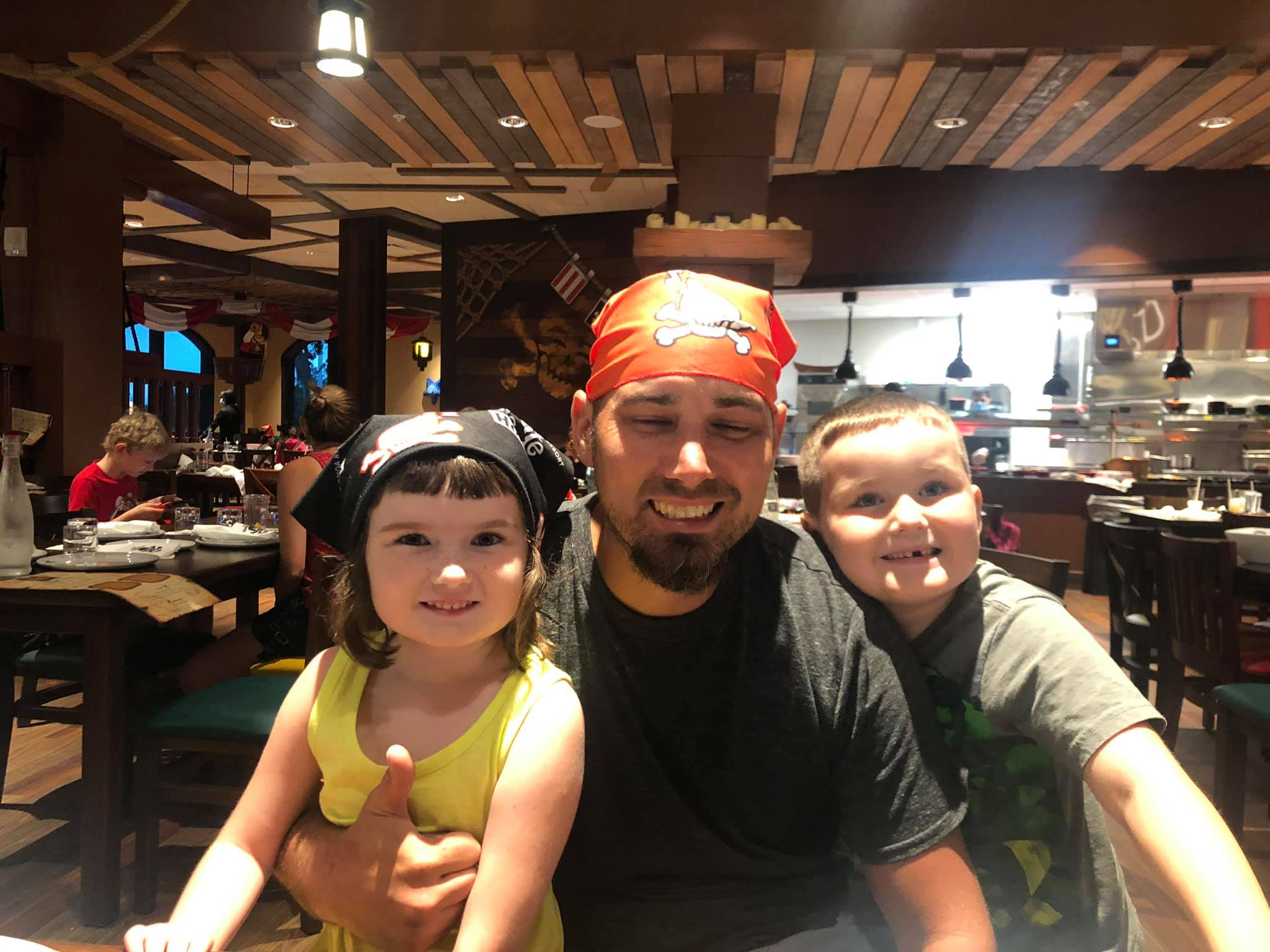 Dad with his two little kids at the table at Shipwreck restaurant at Pirate Island Hotel.   A Guide to LEGOLAND Hotels in Florida