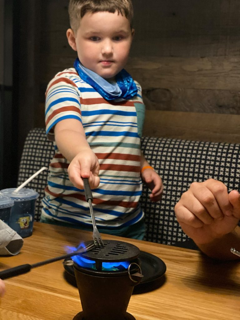 Little boy getting his fire poker warm over the mini table fire in the restaurant of Big Fire. | What to eat at Universal's Citywalk in Orlando