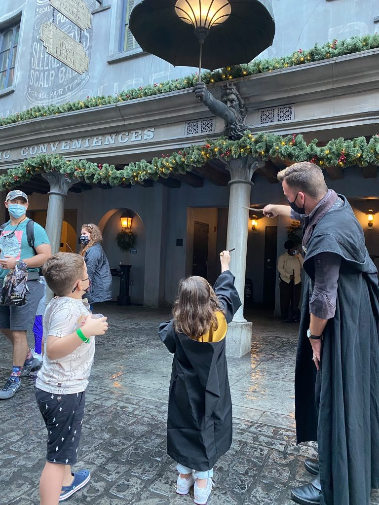 Man dressed as Harry Potter teaching little kids spells with interactive wands in Universal Studios.   A Guide to Universal Studios Orlando with Kids