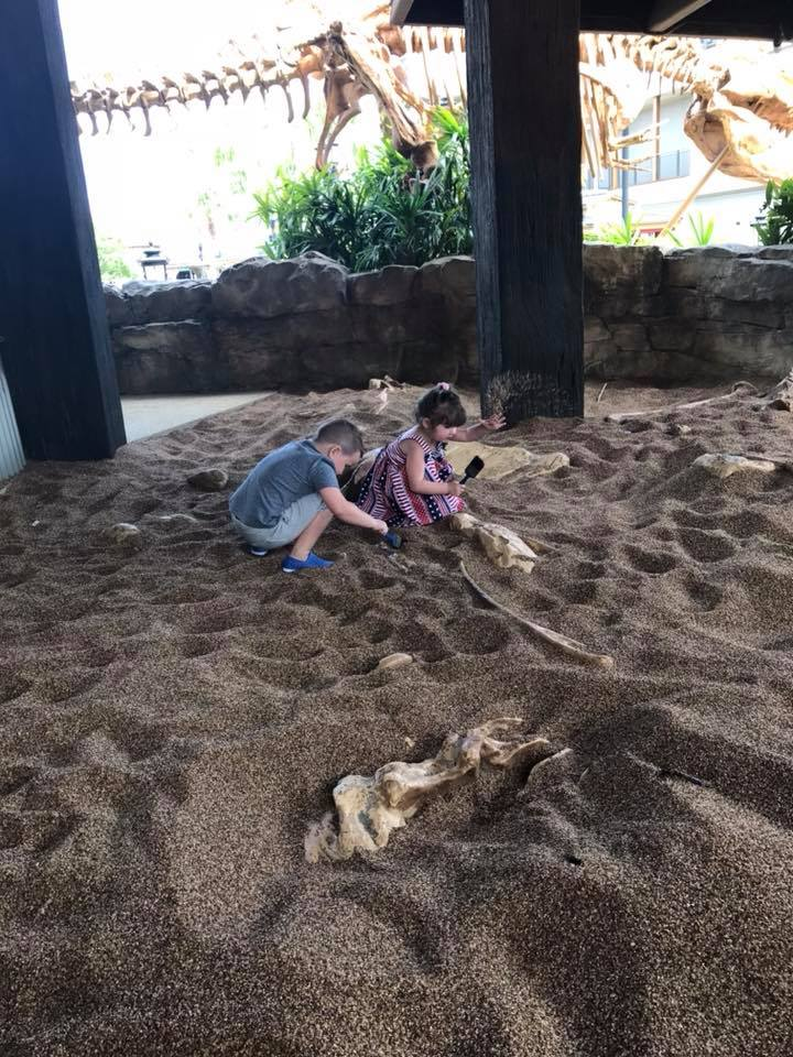 Kids playing in dirt at the T-rex play area in Disney Springs at Disney World.   Disney World- What you need to know.