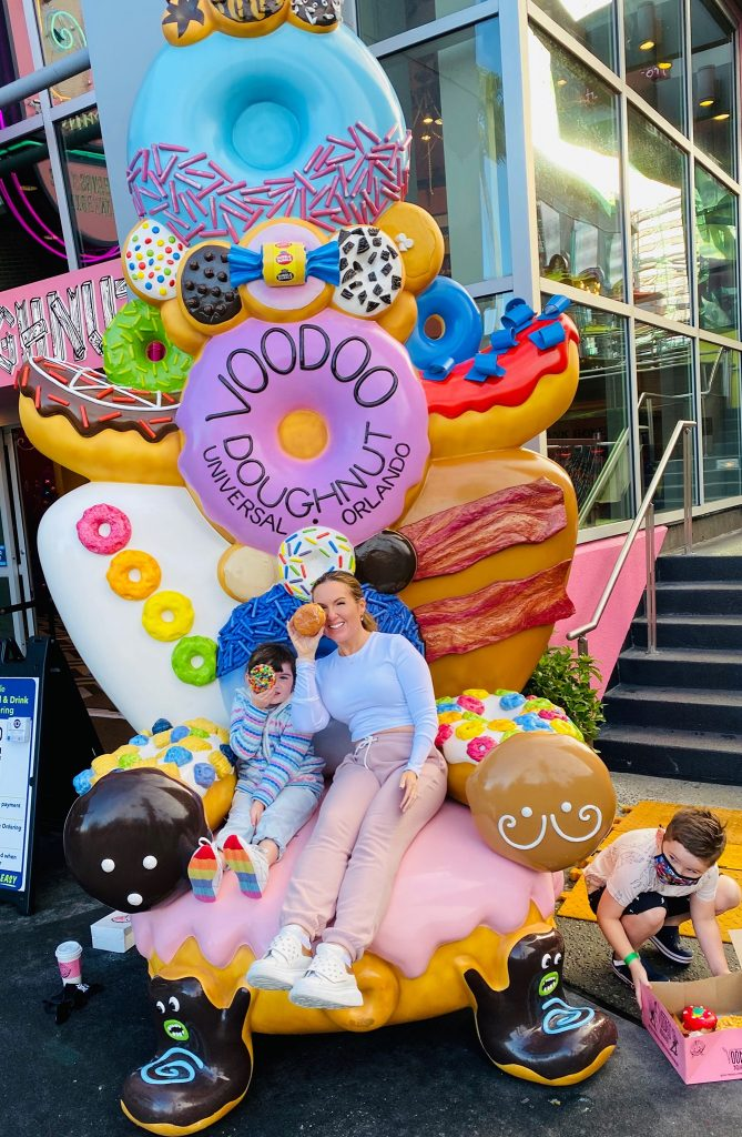 Woman and child posing in front of Voodoo Donut sign, holding up donuts to their eyes.| What to eat at Universal's Citywalk in Orlando