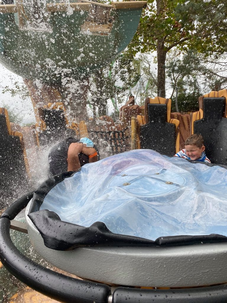 Two riders on the water park ride getting splashed and wet and laughing.   Universal's Islands of Adventure with Kids