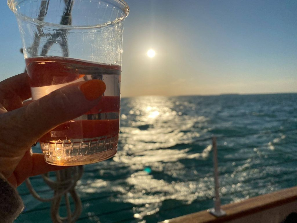 Woman holding cup of wine on cruise ship with sunset and ocean blurred in background.   What to expect on a Key West Sunset Cruise, on a Schooner America Sailboat