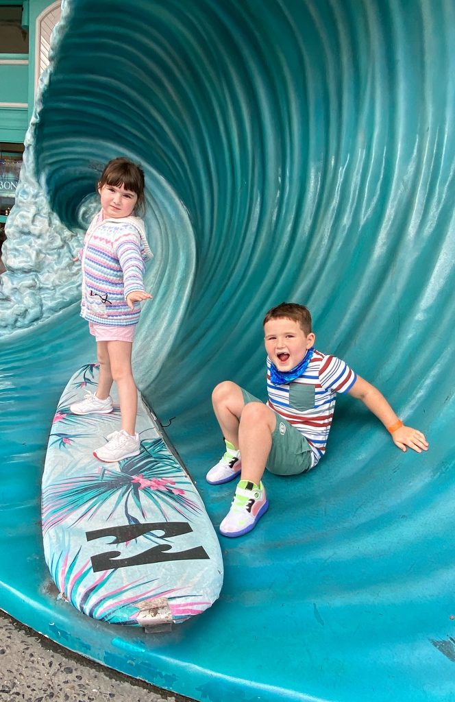 A little boy and little girl posing on a surf board and wave statue. | What to eat at Universal's Citywalk in Orlando